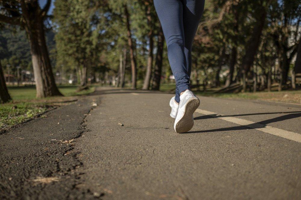 момиче с бели маратонки бяга по шосето с разделителна линия, зелени дървета, поле