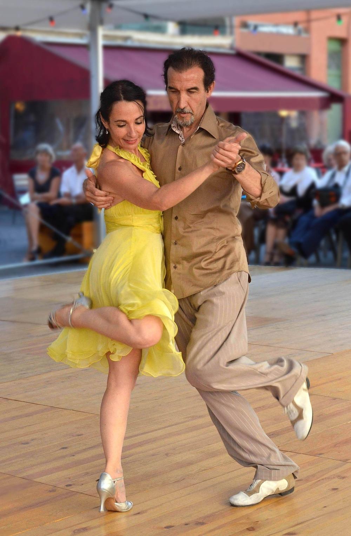 усмихната жена с жълта лятна рокля танцува танго с мъж с риза и панталон в светлокафеви нюанси