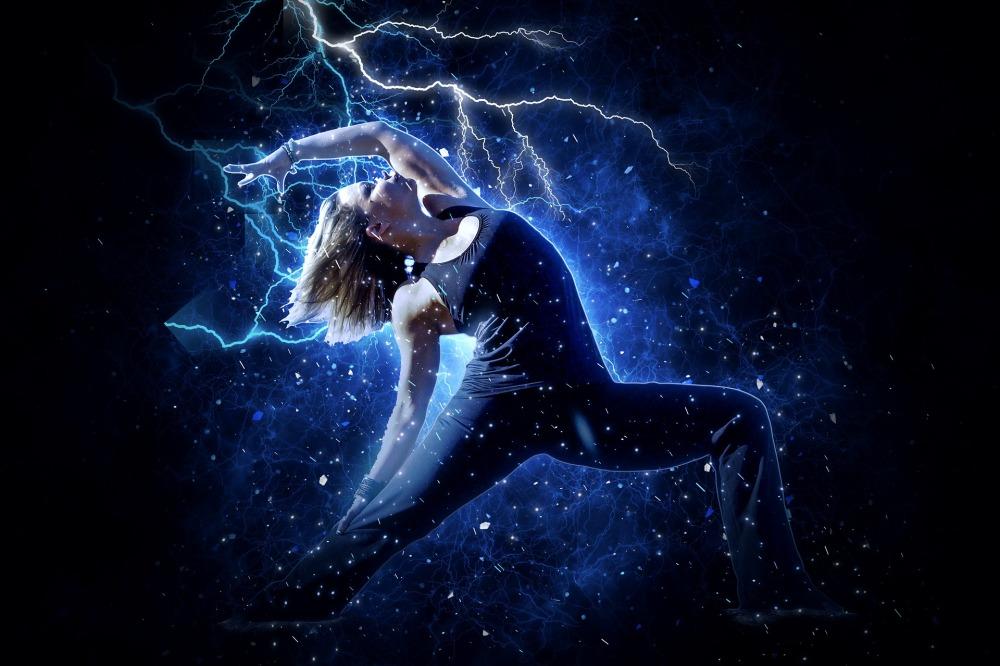 жена в йога поза с гъвкаво тяло, облечена в черни свободни дрехи е вдигнала ръка със замах срещу гръмотевици в небето