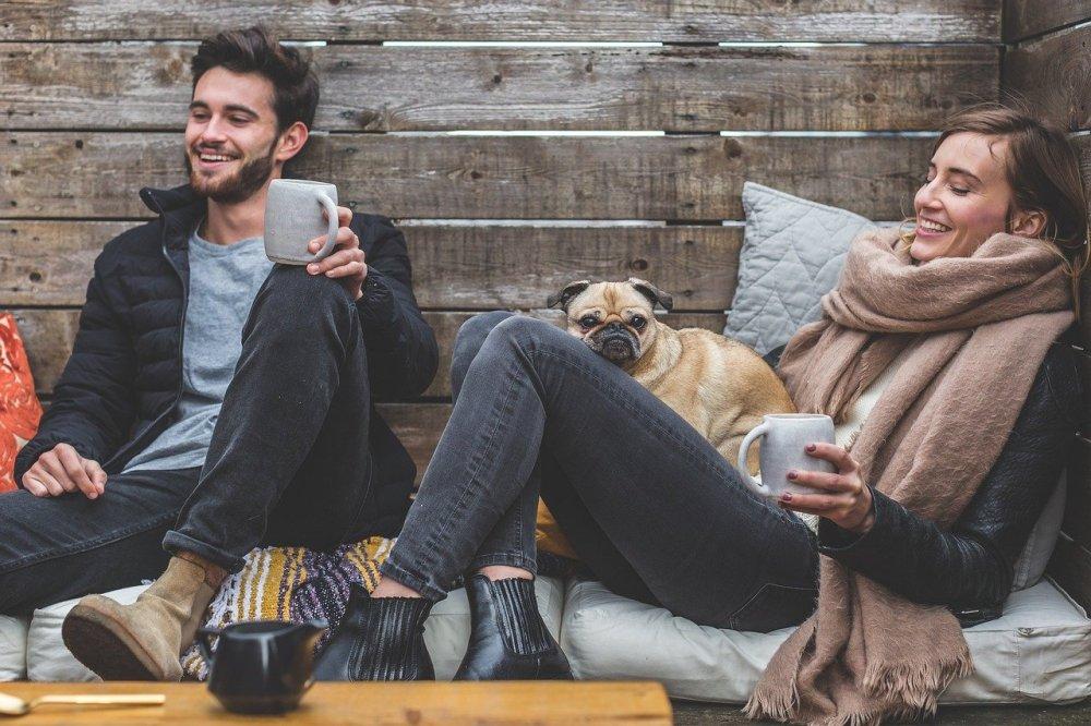 жена и мъж, седнали един до друг, радват се на живота, смеят се, едно малко куче мопс до тях