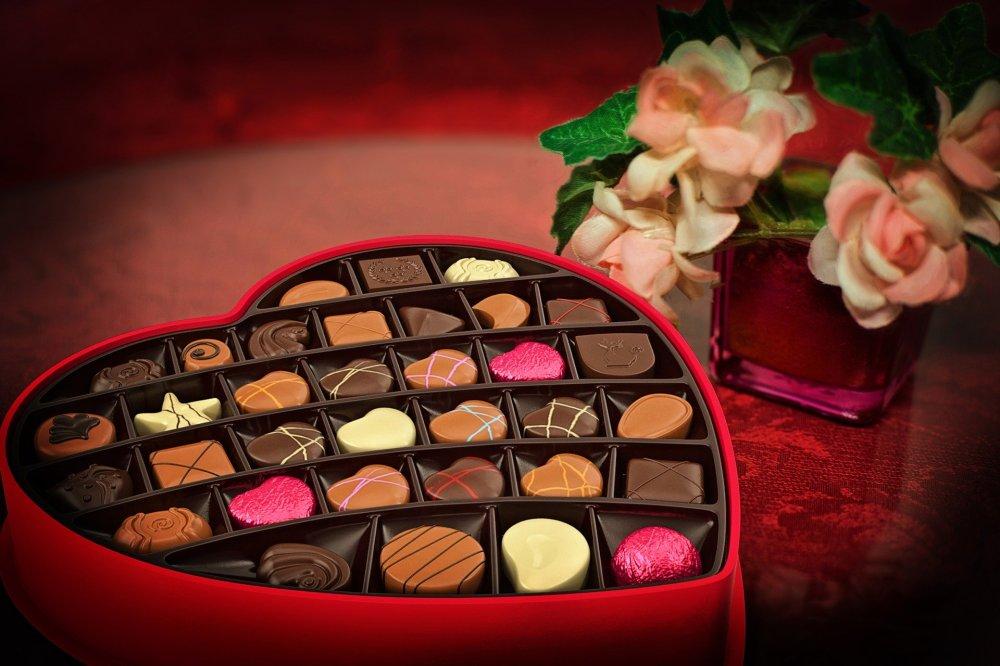 идея за подарък за Свети Валентин, бонбониера във формата на сърце, червена кутия, розови рози във ваза на масата