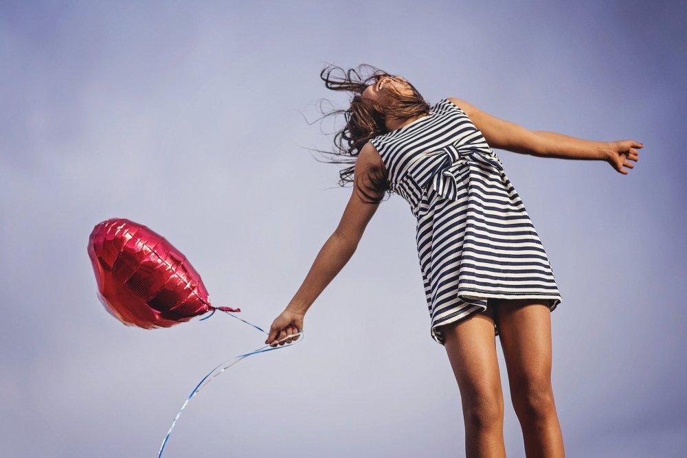 радост от живота, момиче с червено надуваемо сърце в ръка и лятна рокля в моряшки стил, в слънчев ден