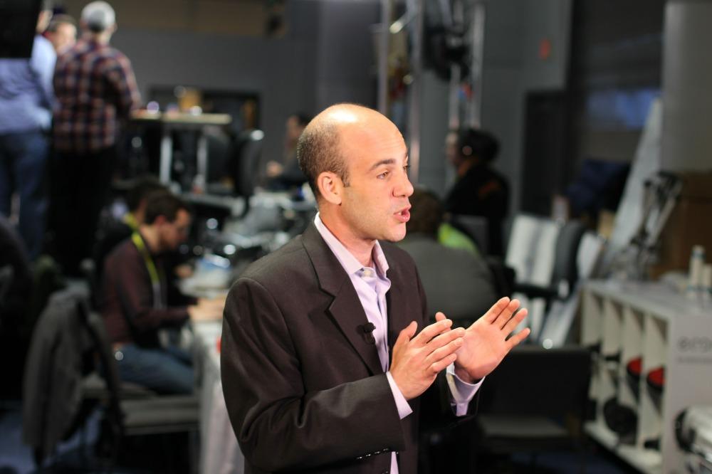 журналист пред публика води предаване, камери, пултове за аудио и видео, хора зад кулисите
