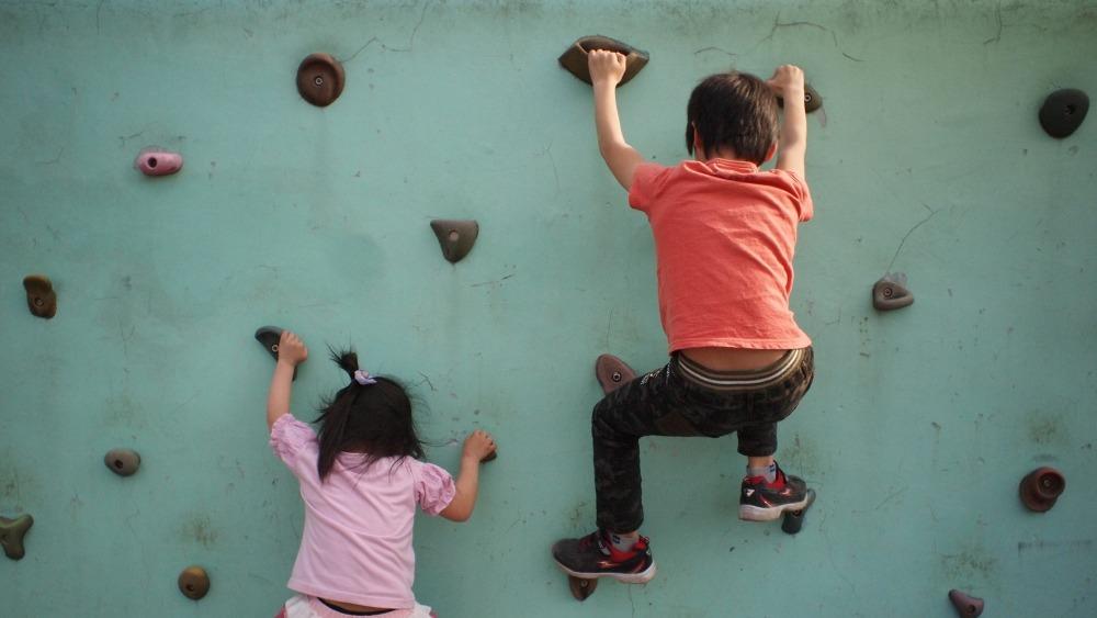 момче и момиче се катерят по стена, захващайки крака и ръце по подпорите, спорт, стена за катерене, детска игра, усмихнати деца