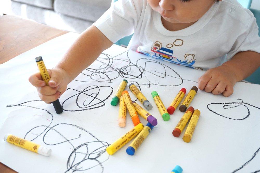 малко дете, голям бял лист хартия, много цветни флумастери, драсканици по листа, детето се учи да рисува