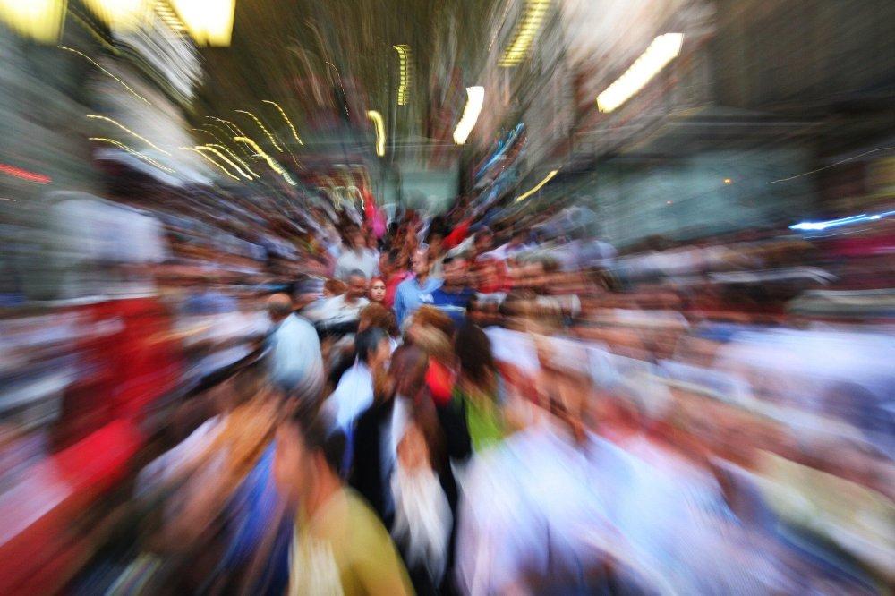 Претъпкана улица, много хора на едно място. Хора с пъстри и многоцветни дрехи на улицата. Голямо движение.