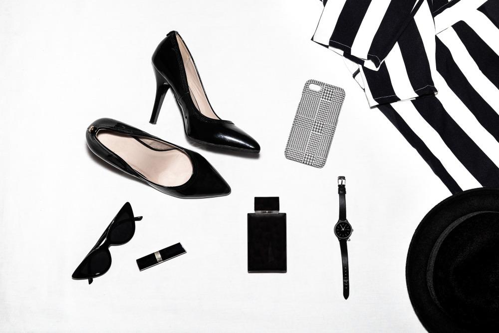 Дамски аксесоари, черни лачени обувки на високи токчета, дамска риза на черно и бяло вертикално райе, черна кадифена широкопола дамска шапка, черен чесовник с тънка каишка, черни слънчеви очила тип котешко око, парфюм в черна опаковка, стик червило в черна опаковка, калъф за телефон на черни и бели пепити