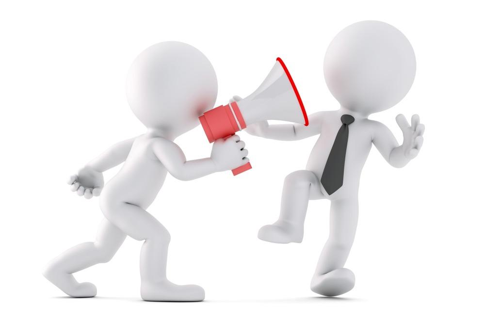Двама души разговарят в офиса, единият е с черна вратовръзка и е подскочил от изненада, а другият е с високоговорител в ръка и му вика