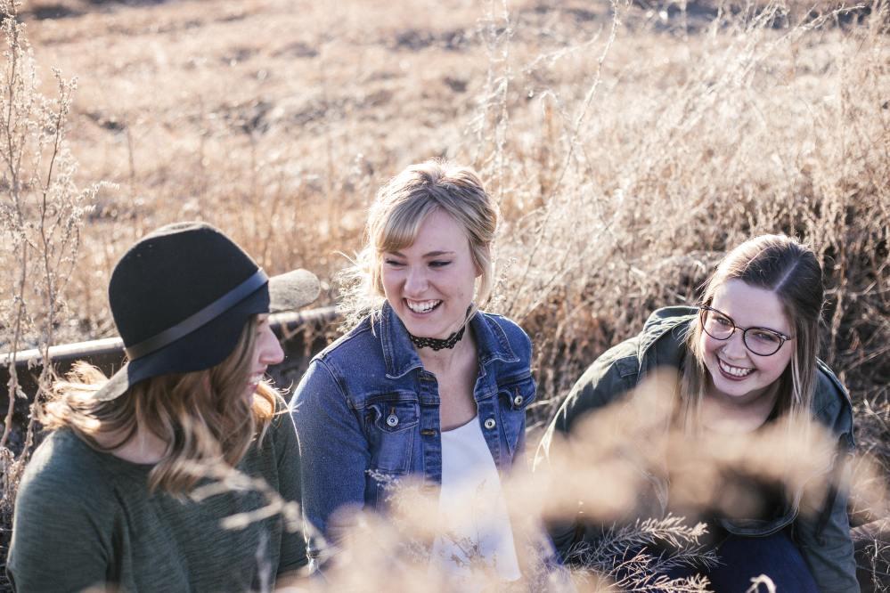 Три момичета седят и си говорят на открито в хубав слънчев летен ден. Момиче с широкопола черна шапка, момиче с едра рамка очила, момиче с черно колие по врата.