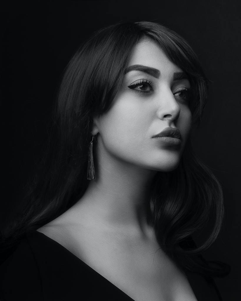 Чернобяла ретро снимка на красива и гримирана жена с дълга черна коса, черна очна линия, бадемови очи, плътни устни, дълги висящи обеци