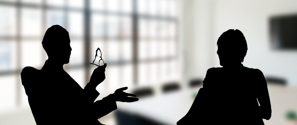 Двама души седят в заседателна зала и разговарят. Работна атмосфера, офис. Единият човек размахва ръце и държи очила.