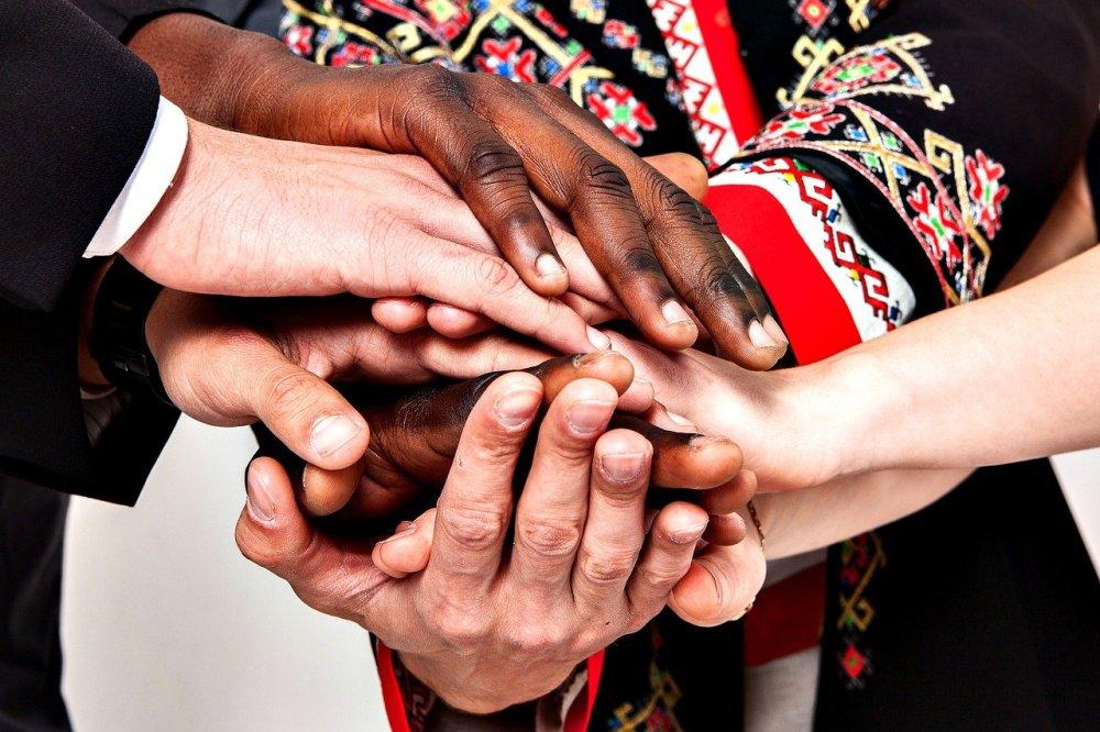 Хора от различни националности и с различни етнически носии са хванали ръцете си една върху друга. Хора от различни раси. Съгласие и общуване.