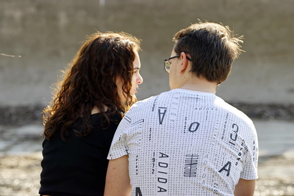 Двойка мъж и жена води разговор на открито, седнали на пейка през лятото, в слънчево време. Мъжът е с очила, а жената е с дълга кестенява и къдрава коса