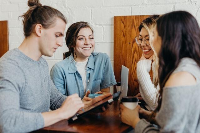 Четирима усмихнати млади хора са седнали на малка маса и общуват, смеейки се. Момиче с големи очила с кръгла рамка. Таблет и лаптоп.