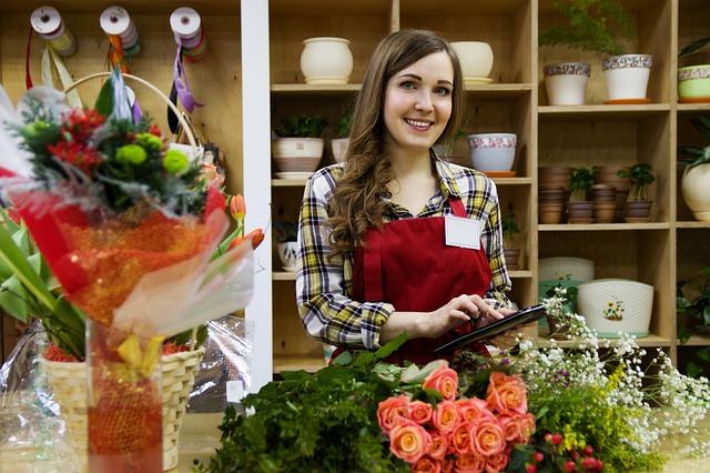 Убедителна комуникация, как да убеждаваме, усмихната продавачка в магазин за цветя, с букети от рози на масата пред нея, продавачка с таблет в ръка