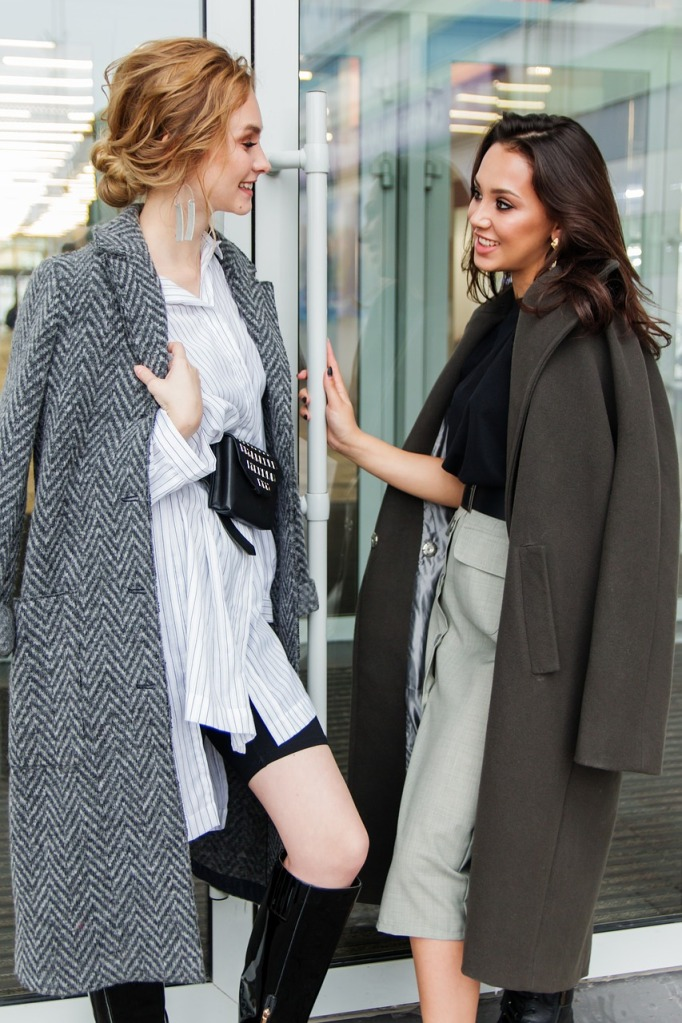 две красиви и модно облечени жени разговарят в модерна стъклена сграда, високи черни ботуши, две дълги елегантни палта, хубави прически