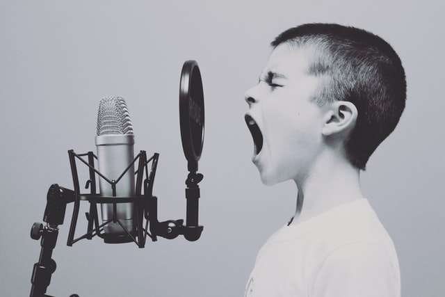 снимка в черно и бяло, момче е застанало пред голям ретро микрофон и е отворило широко уста, силен вик