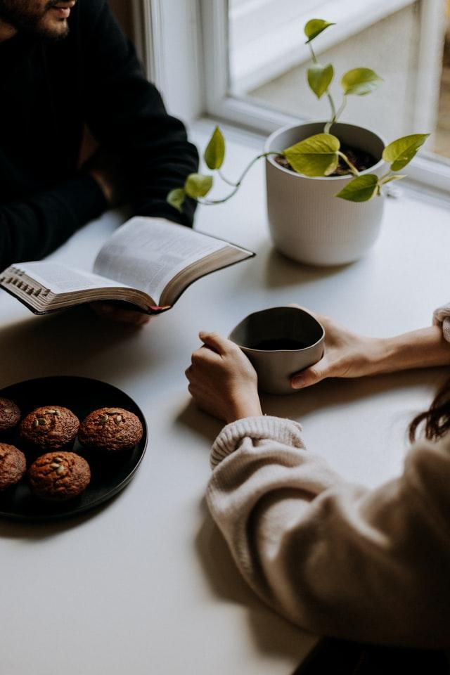 мъж и жена пият кафе и разговарят, седнали на квадратна бяла маса, на която има зелено растение в бяла ваза и чиния от черен порцелан с бисквитки, мъжът държи отворена книга, жената държи чаша топло кафе