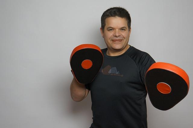 боксьор с ръкавици в черно и оранжево е заел отбранителна позиция, готов да се бори