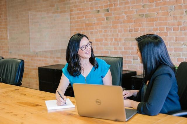 две жени са седнали на два кожени офис стола пред голямо бюро пред лаптоп, едната си ноди бележки и слуша активно