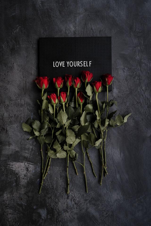десетина аленочервени рози са положени върху надпис Обичай себе си