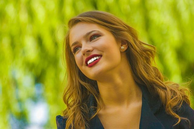 широко усмихната жена с червило във винен цвят и идеално бели зъби, с дълга светло кестенява коса на вълни и сако в морско син цвят