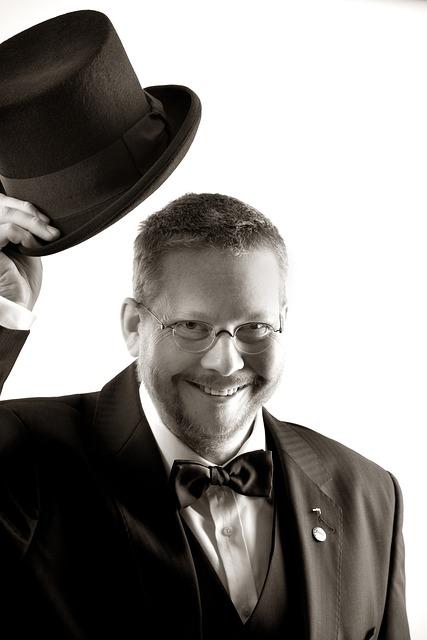 снимка в черно и бяло, господин, облечен с бяла риза, във фрак и цилиндър и с папийонка, с очила в овална форма, е повдигнал цилиндъра за поздрав, в знак на уважение