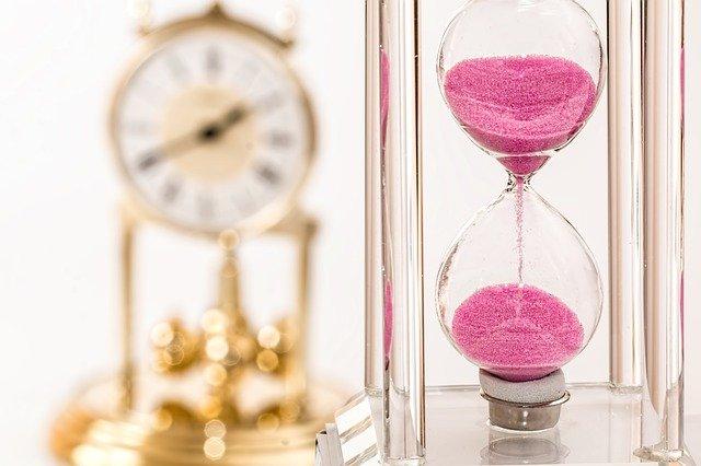 снимка с два часовника, швейцарски часовник с въртящи се тежести и стъклен пясъчен часовник с розов пясък