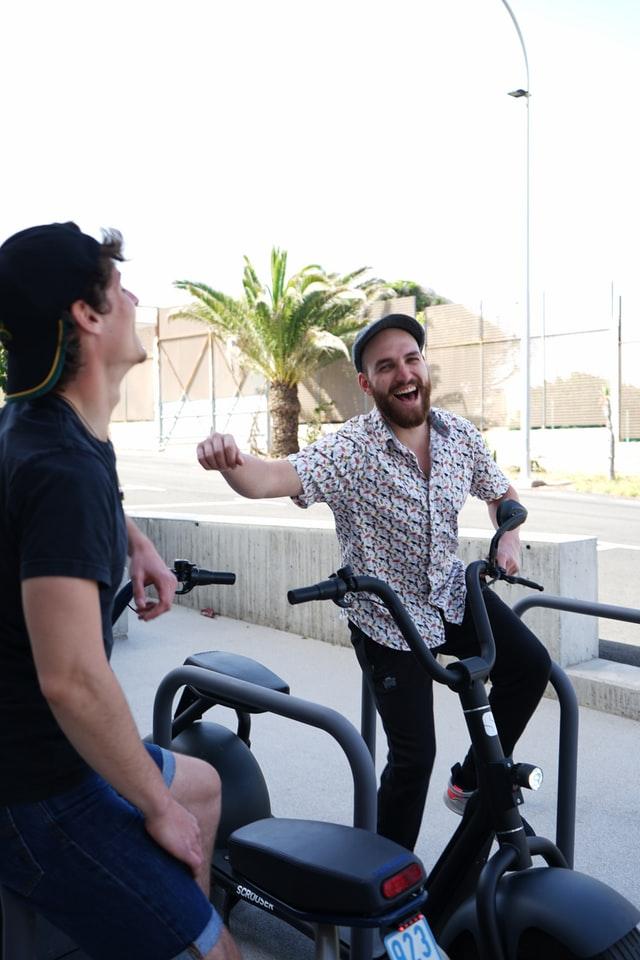 двама мъже с каскети са седнали на велоергометри във вътрешен двор с палма и мерят силите си