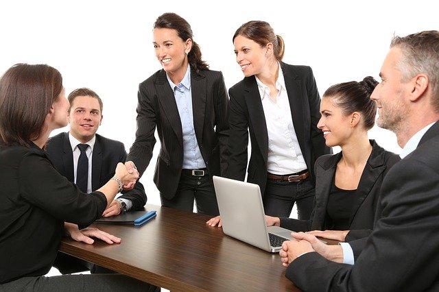 шестима служителя в черни сака и костюми са седнали в офиса около голямо бюро и дискутират, четири жени и двама мъже, две от служителките си стискат ръцете с усмивка