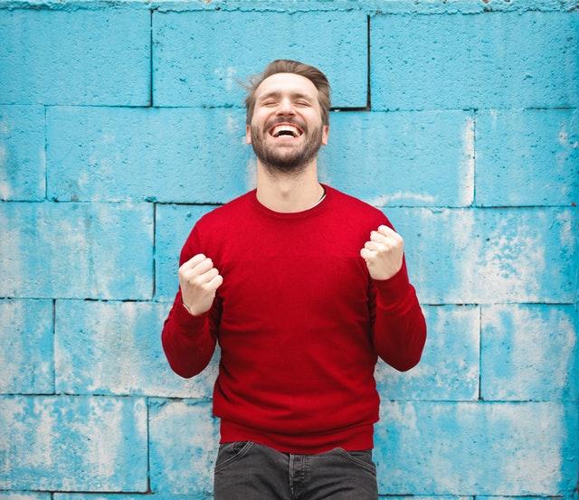 млад русокос мъж, облечен в ярко червен пуловер и светлосиви дънки е стиснал радостно и победоносно юмруци и е показал зъбите си в широка усмивка