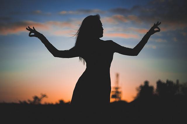 женски силует на дългокоса жена, разперила ръцете си като криле, на фона на красив летен залез