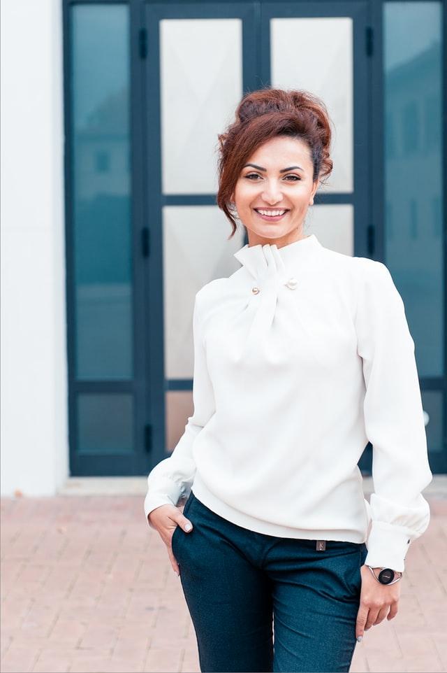широко усмихната жена с вдигната на кок коса, облечена в бяла официална блуза с буфан ръкави и черен елегантен панталон от коприна, с елегантен кръгъл часовник