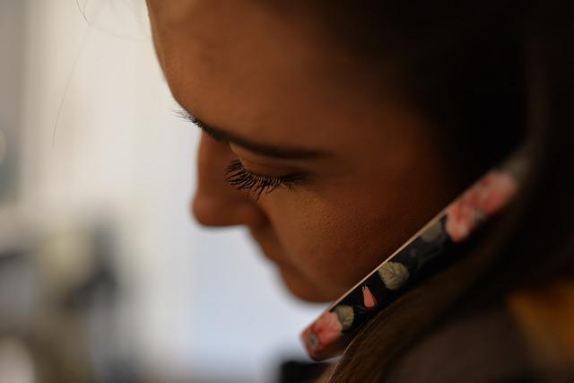 младо момиче с тъмна коса разговаря по мобилния си телефон, който е със защитен калъф с розови рози на черен фон