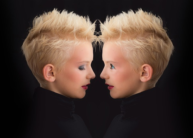 две късо подстригани и изрусени сестри близначки са застанали една срещу друга и се гледат, едната е притворила очи, другата е с отворени и усмихнати очи