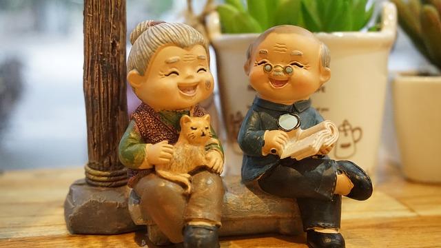 две порцеланови фигурки на баба и на дядо в седнало положение, бабата държи котка в скута си, дядото държи разтворена книга на коленете си и чете с лупа
