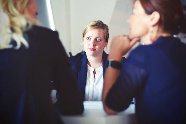 три жени в бизнес облекло са седнали около масата в залата за заседания, двете от тях разговарят, третата ги слуша внимателно