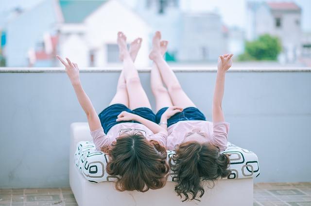 две млади момичета са легнали по гръб върху ратаново легло на широка тераса и съзерцават лятното небе, като са направили и двете знака за победа с ръцете си