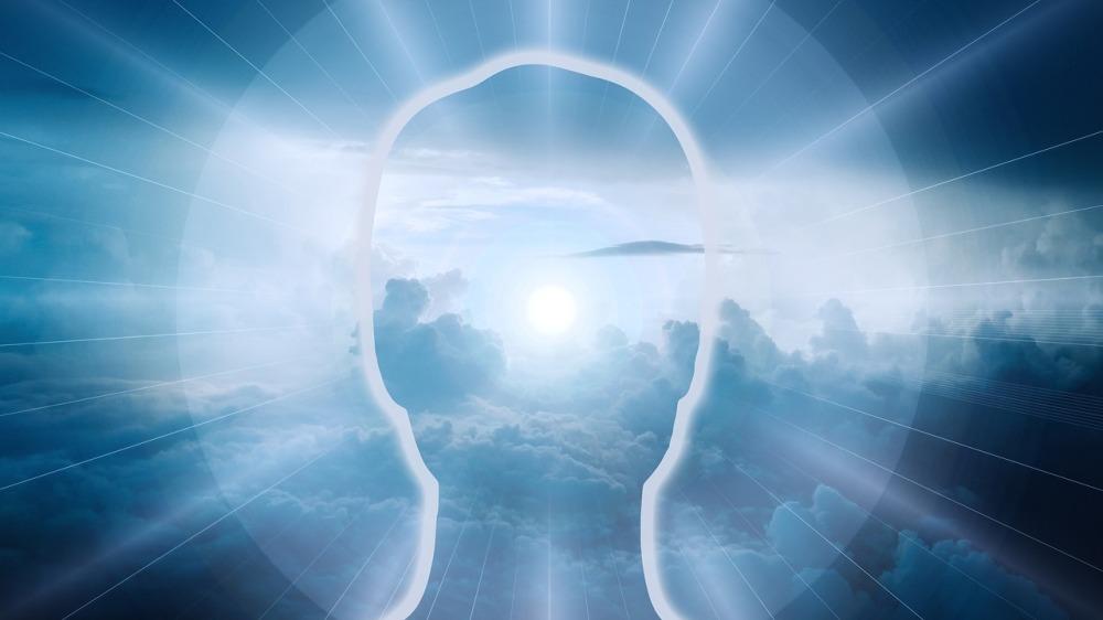 силна бяло-синкава светлина преминава през силует на човешко лице без очи прозрачен силует, през който преминава силна светлина иззад бели облаци