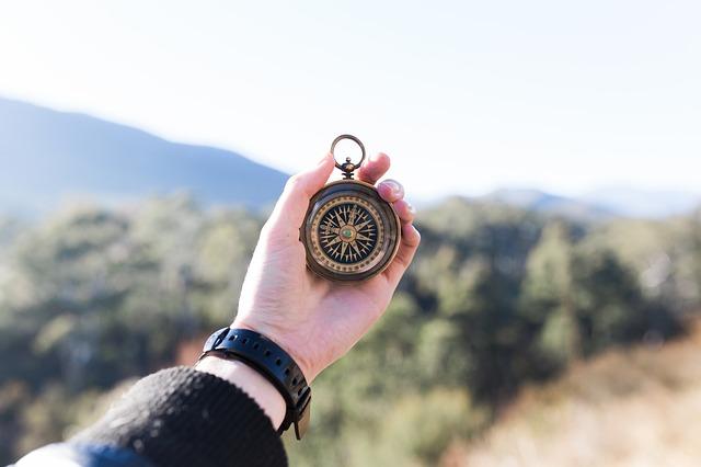 ръка на млад мъж държи старовремски компас, за да се ориентира в гориста и планинска местност