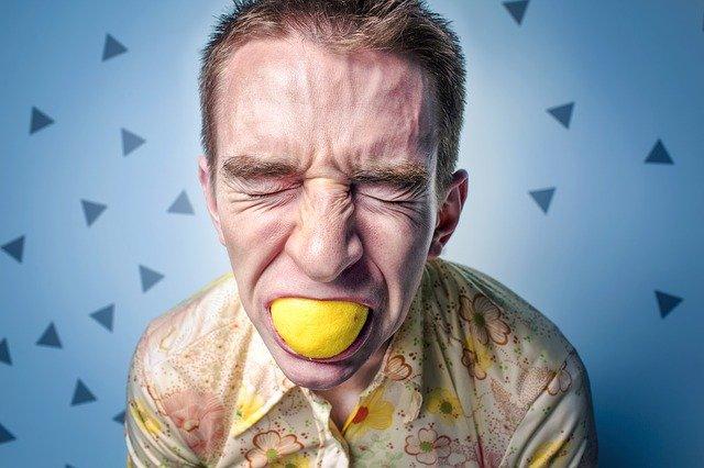 мъж с лице, покрито от бяла пудра е захапал лимон с кората и е направил гримаса заради горчивината му, фонът отзад е синя стена с декоративни триъгълничета