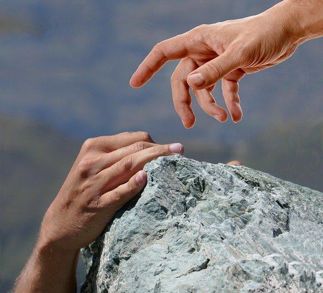 две човешки ръце се протягат една към друга, един човек спасява друг на ръба на планинската бездна